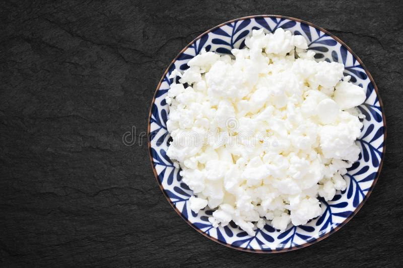 An overhead photo of fresh natural cottage cheese in a floral ceramic bowl on the black stone desk. Organic eco healthy meal, royalty free stock images