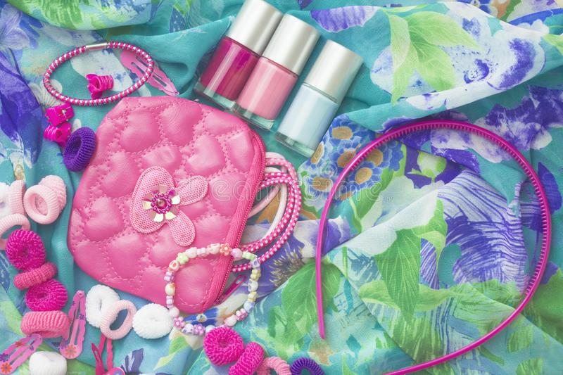 An overhead photo of little girl accessories, lifestyle set. Headband and nail polish. A group of girlish teenager accessories and stock images
