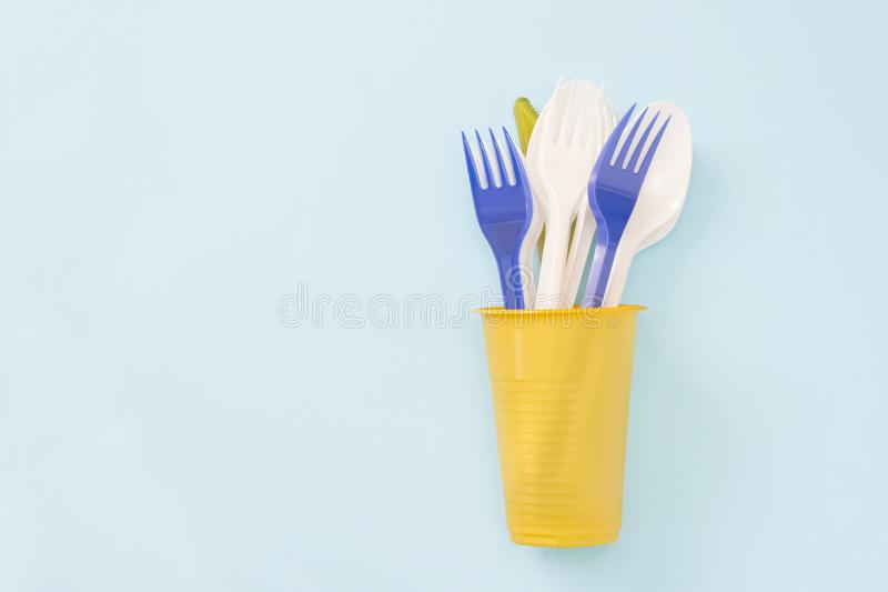 An overhead photo of plastic garbage. Plastic disposable tableware, spoon, forks in cup. Zero waste, environmental pollution. Save stock photography