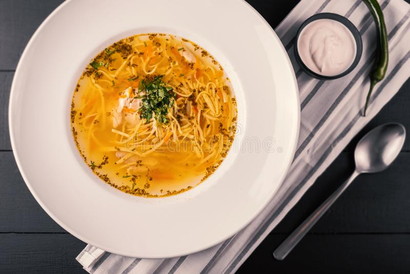 An overhead photo of a plate of chicken and noodles soup, shot from above on a dark rustic texture and a copy space. stock photo