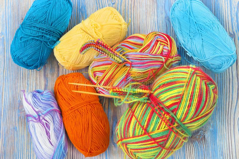 An overhead photo of the working place. Knitting needles and melange rainbow multicolor cotton yarn ball on the rustic wooden tabl royalty free stock photography