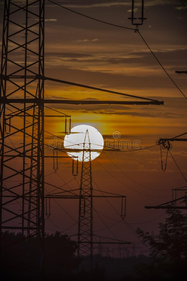 Overhead power line with rising sun. In summer 2014 royalty free stock photo