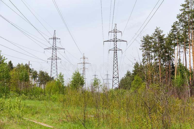 Overhead power lines among of the spring forest. Several overhead power lines with steel lattice structures transmission towers and reinforced concrete poles royalty free stock photography