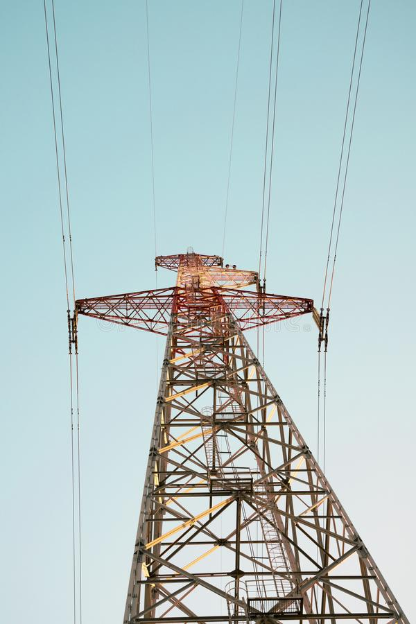 Overhead power transmission line tower with strange concrete foundation during construction. High voltage electric pole stock image