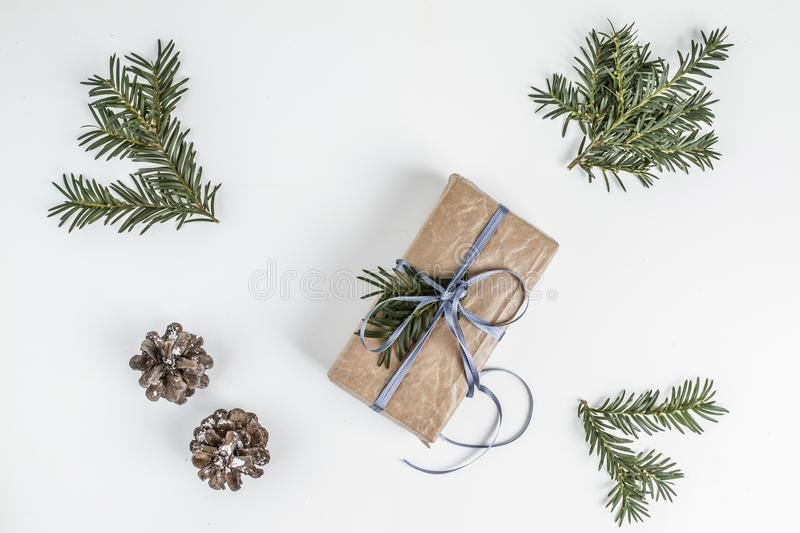 OVERHEAD RUSTIC HOMEMADE PRESENT BOX. CHRISTMAS ORNAMENTS ON WHITE BACKGROUND royalty free stock photo