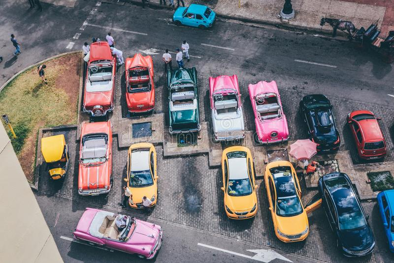 Overhead shot of assorted cars in different colors in a parking lot. An overhead shot of assorted cars in different colors in a parking lot stock photos