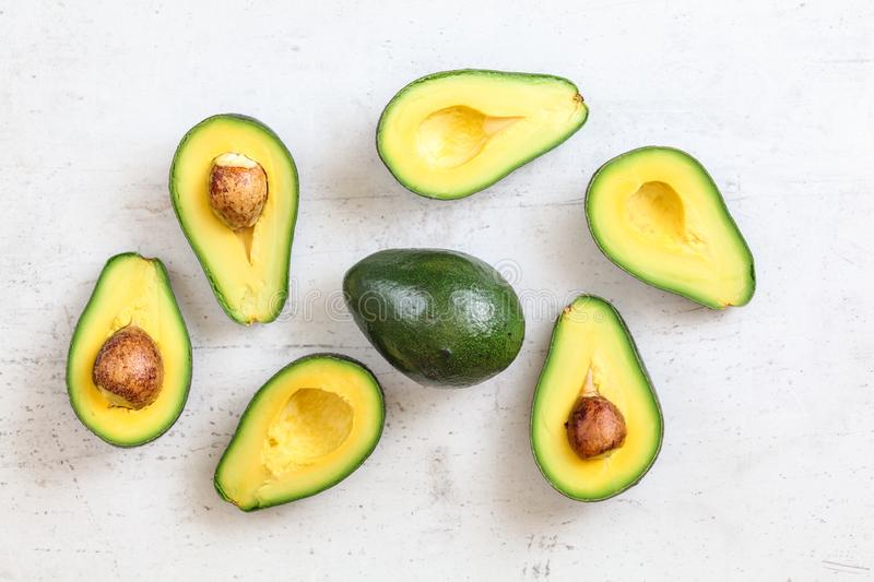 Overhead shot - avocados halves, some with seed, whole green pear in middle, on white working board.  royalty free stock photo