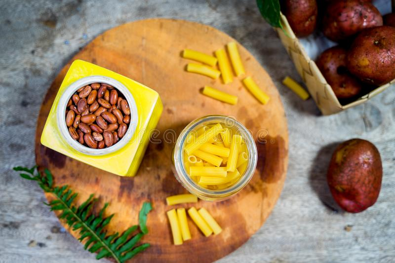 Overhead shot of beans in yellow ceramic tin. Potato, pinuts, penne, cutting, boad royalty free stock photo