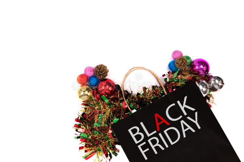 Overhead shot of black paper bag with black friday word and christmas decorations on white background. stock photo
