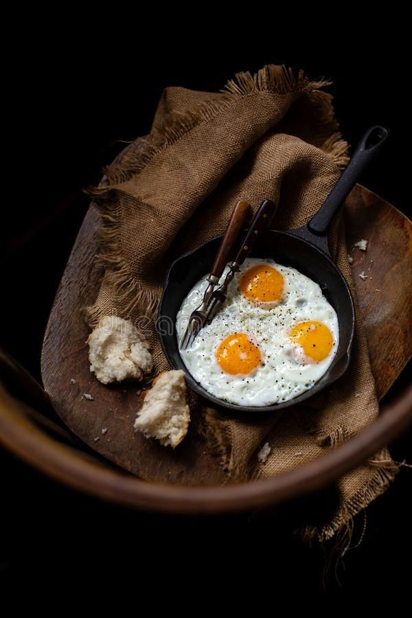 Overhead shot of cast-iron pan with three fried eggs sprinkled with black pepper royalty free stock photo