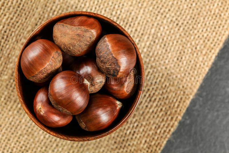 Overhead shot - chestnuts in small wooden bowl on jute tablecloth.  royalty free stock image