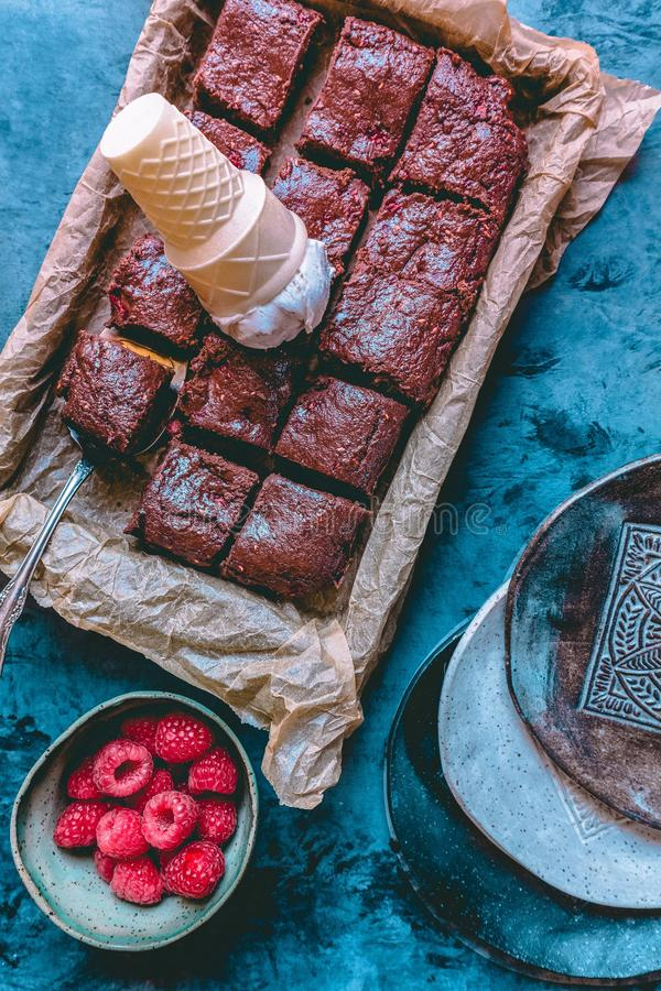 An overhead shot of a chocolate cake with an ice-cream stuck in it and raspberries on the side royalty free stock photo