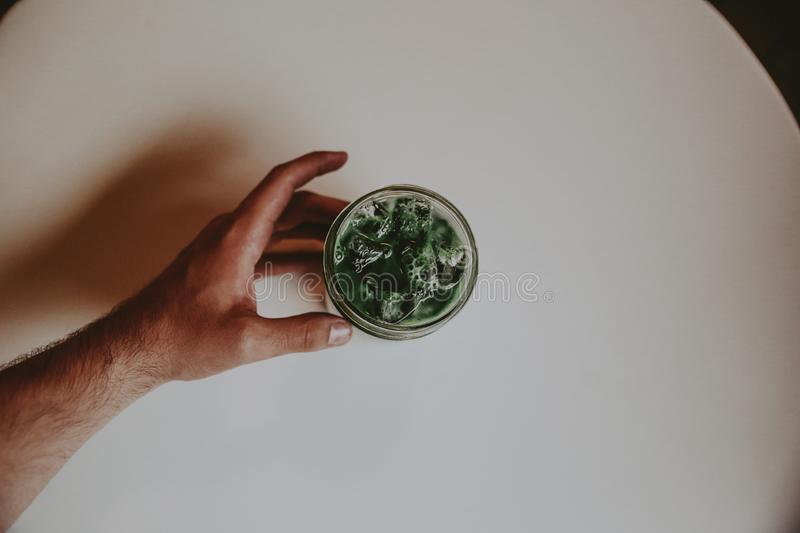 Overhead shot of a coffee Glasse with a male`s hand holding it on a white background stock image