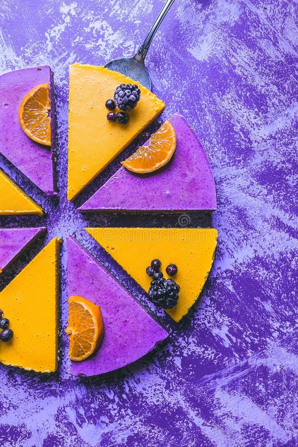 Overhead shot of a colorful lemon and berry cake with a rustic purple background royalty free stock images