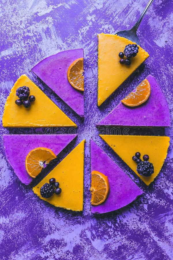 Overhead shot of a colorful lemon and berry cake with a rustic purple background royalty free stock photography