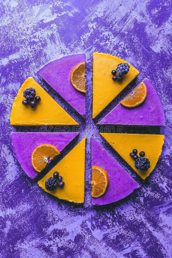 Overhead shot of a colorful lemon and berry cake with a rustic purple background royalty free stock photo