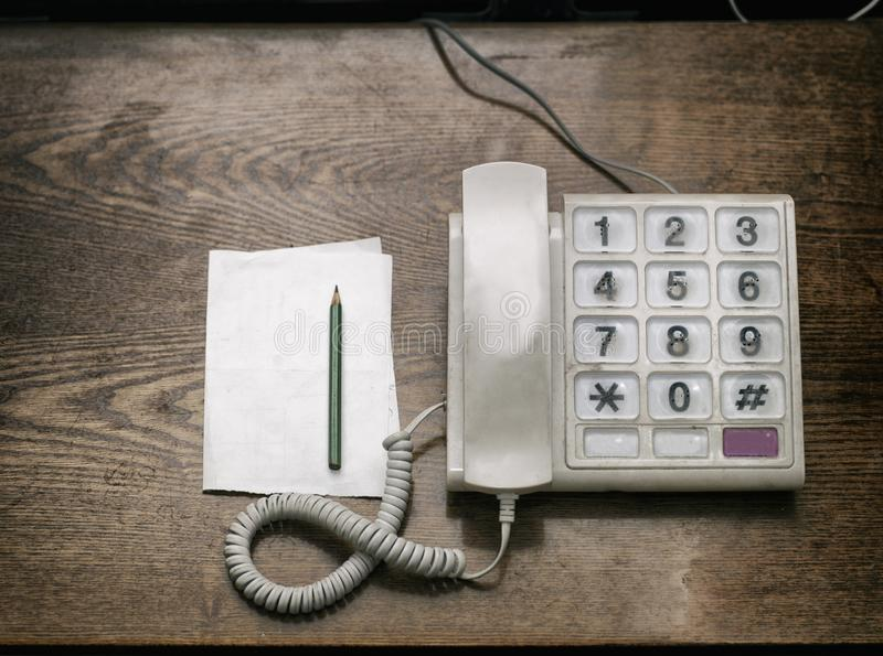 Corded telephone, pencil and paper stock photo