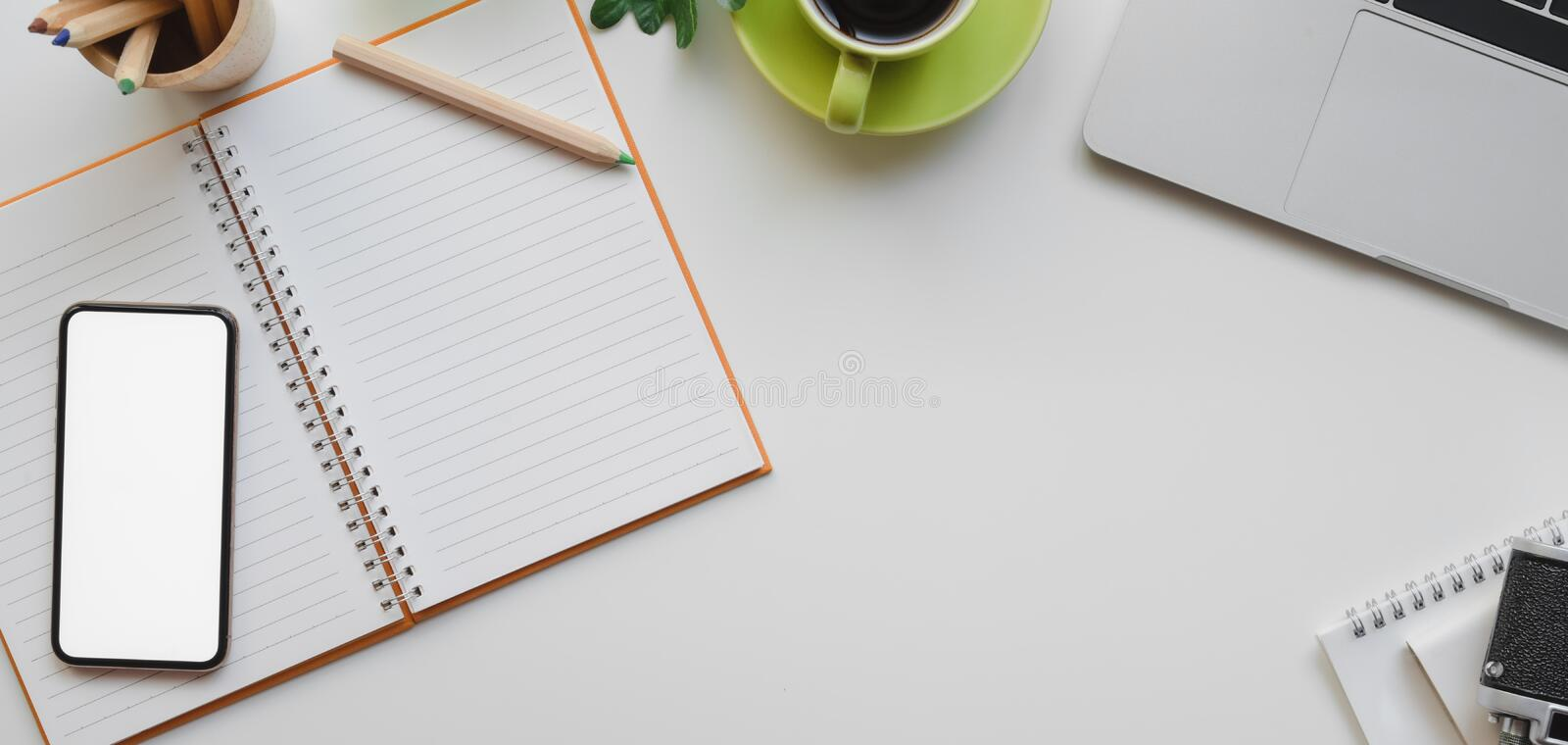 Overhead shot of designer workplace with laptop computer, mock up smartphone and office supplies. On white table background stock images