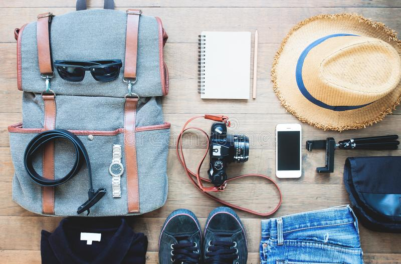 Overhead shot of essentials for traveler. Outfit of young man traveler, camera, mobile device, sunglasses. Travel concept stock image