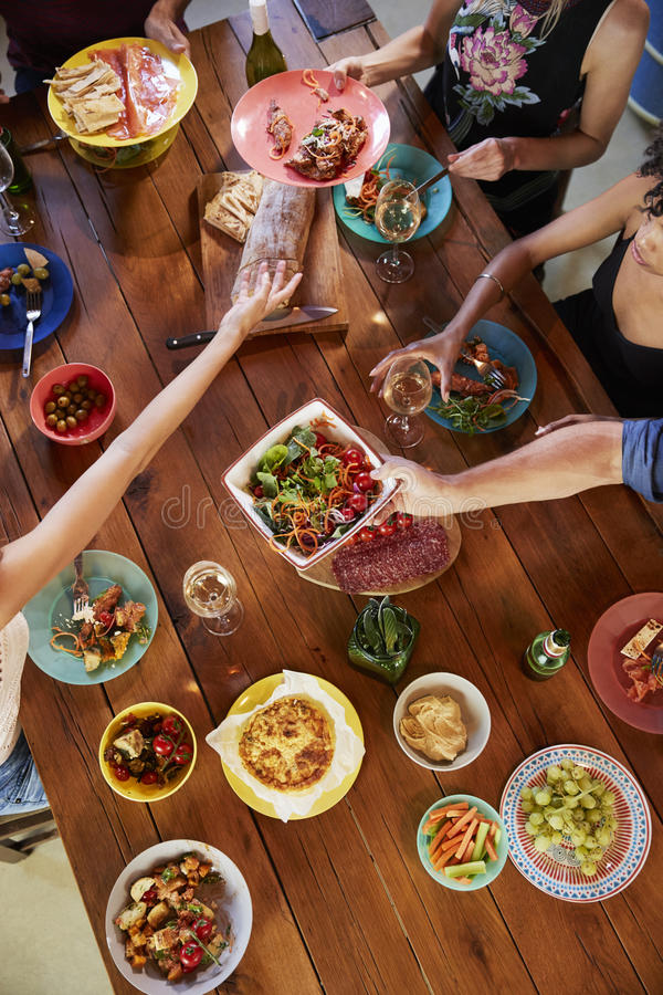 Overhead shot of friends passing food across a dinner table royalty free stock images