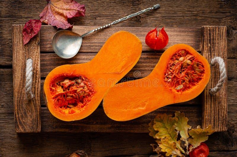 Overhead shot of halved orange pumpkin on rustic wooden tray. Dieting healthy food stock photo