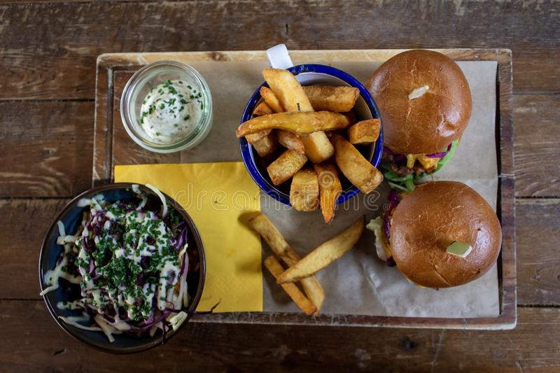 Overhead shot of hamburgers and french fries near sauce and a salad on a wooden tray royalty free stock photos