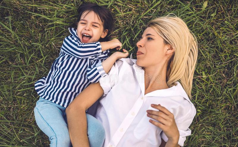 Overhead shot of happy pretty funny woman playing and lying on green grass outdoor with her cute little girl. Loving mother and royalty free stock image