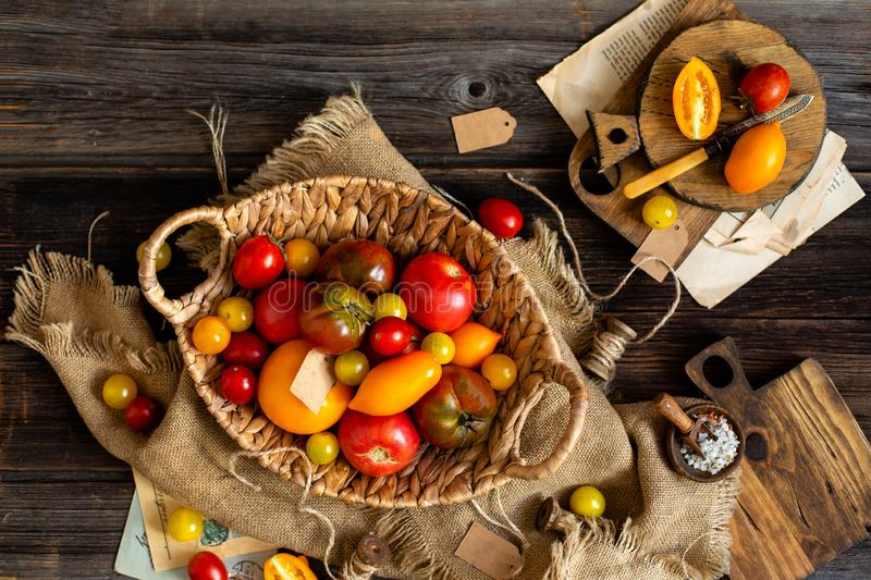 Overhead shot of homegrown assorted red, yellow, orange tomatoes in wicker straw basket. On sackcloth on rustic wooden table, autumn harvesting stock image