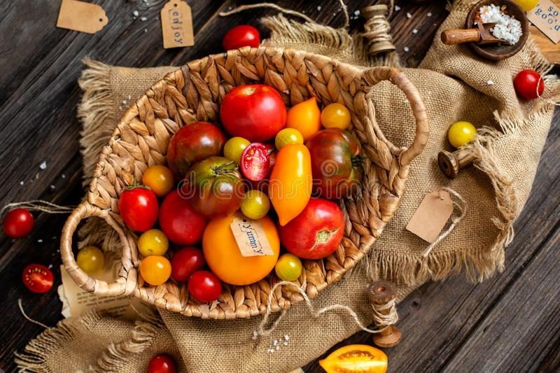 Overhead shot of homegrown assorted red, yellow, orange tomatoes in wicker straw basket. On sackcloth on rustic wooden table, autumn harvesting stock photo