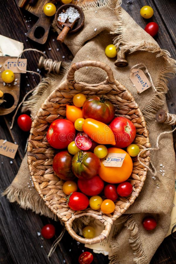 Overhead shot of homegrown assorted red, yellow, orange tomatoes in wicker straw basket. On sackcloth on rustic wooden table, autumn harvesting stock images