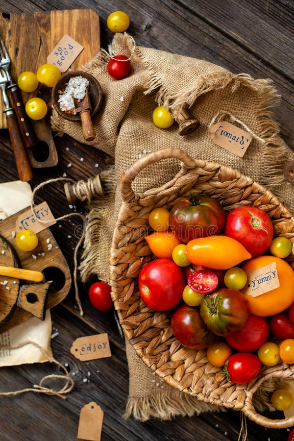 Overhead shot of homegrown assorted red, yellow, orange tomatoes in wicker straw basket. On sackcloth on rustic wooden table, autumn harvesting royalty free stock images
