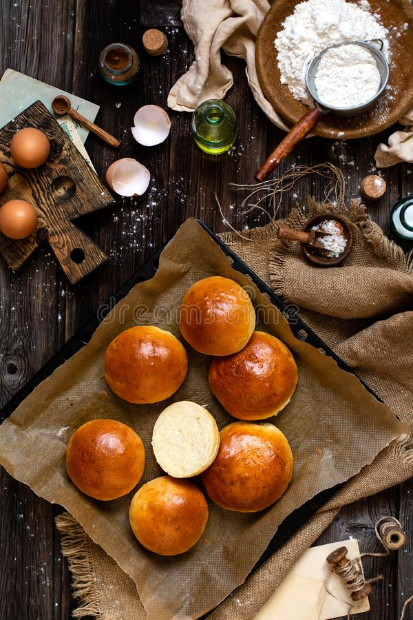 Overhead shot of homemade baked tasty buns for burger or breakfast. Overhead shot of homemade cut baked tasty yeast dough buns on baking tray with parchment stock photography