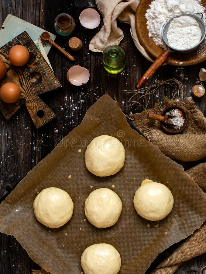 Overhead shot of homemade baked tasty buns for burger or breakfast. Overhead shot of homemade unbaked egg washed yeast dough buns on baking tray with parchment royalty free stock images
