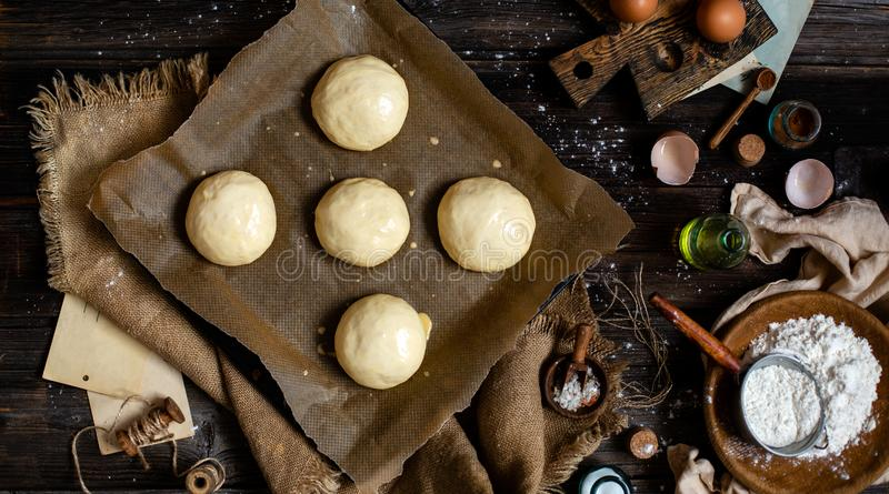 Overhead shot of homemade baked tasty buns for burger or breakfast. Overhead shot of homemade unbaked egg washed yeast dough buns on baking tray with parchment royalty free stock photography