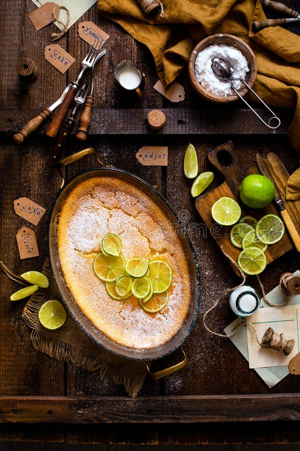 Overhead shot of homemade casserole, pudding, cheesecake, tart, pie or mousse with slices of lime in oval glass baking dish royalty free stock photos
