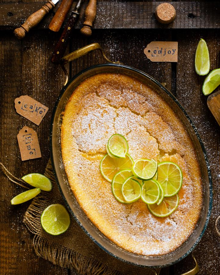 Overhead shot of homemade casserole, pudding, cheesecake, tart, pie or mousse with slices of lime on top. In oval glass baking dish stands on rustic brown table stock photos