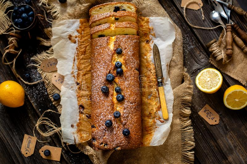 Overhead shot of homemade tasty lemon baked cake with blueberries on paper and sackcloth royalty free stock images