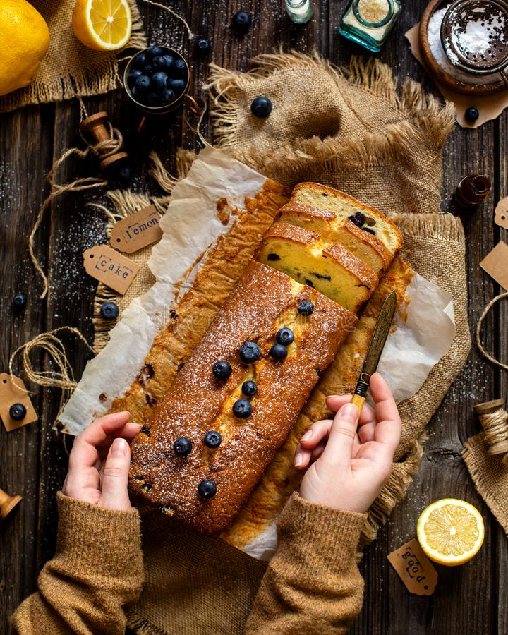 Overhead shot of homemade tasty lemon baked cake with blueberries on paper and sackcloth stock images