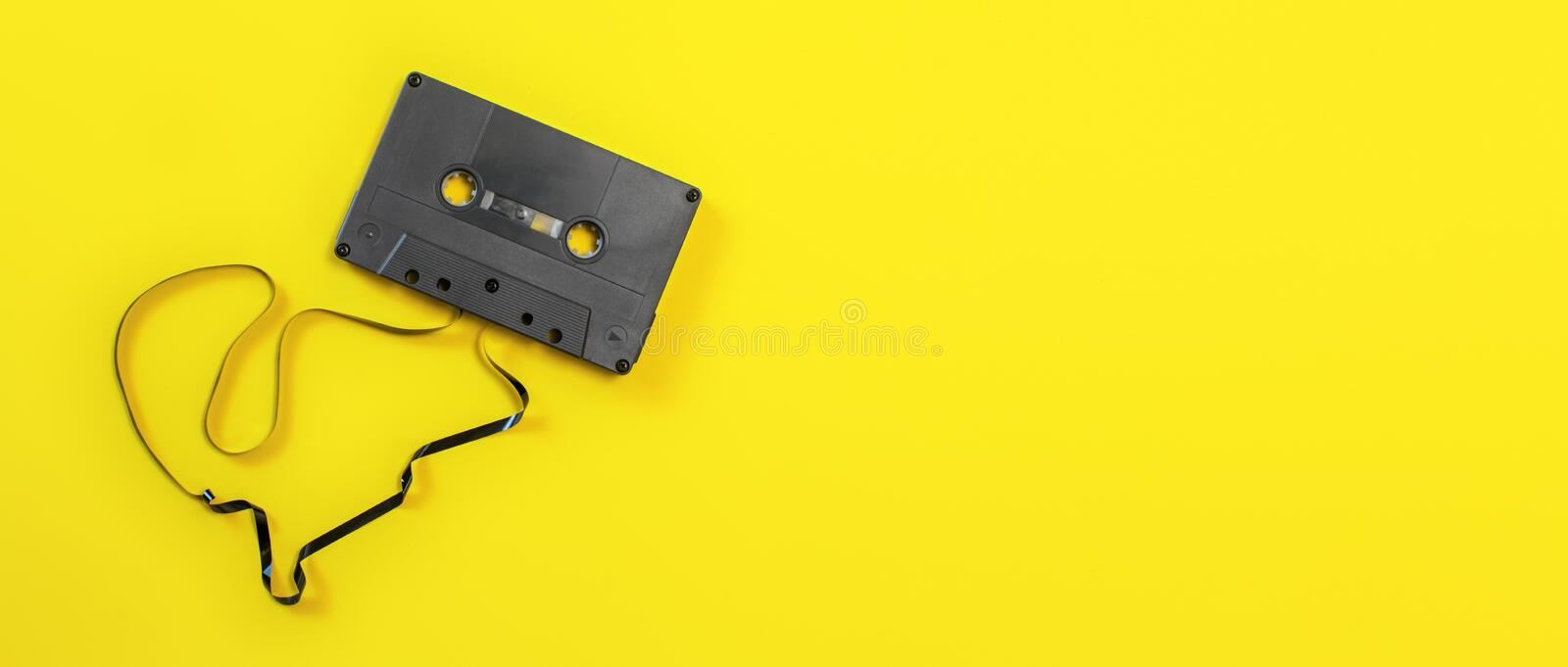 Overhead shot - magnetic audio cassette with some tape out, on yellow board, wide banner space for text on right side.  royalty free stock image
