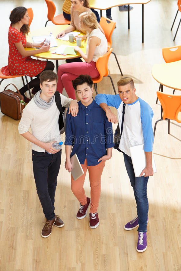 Overhead Shot Of Male Students Standing In Cafeteria. Wearing There Backpacks stock photos