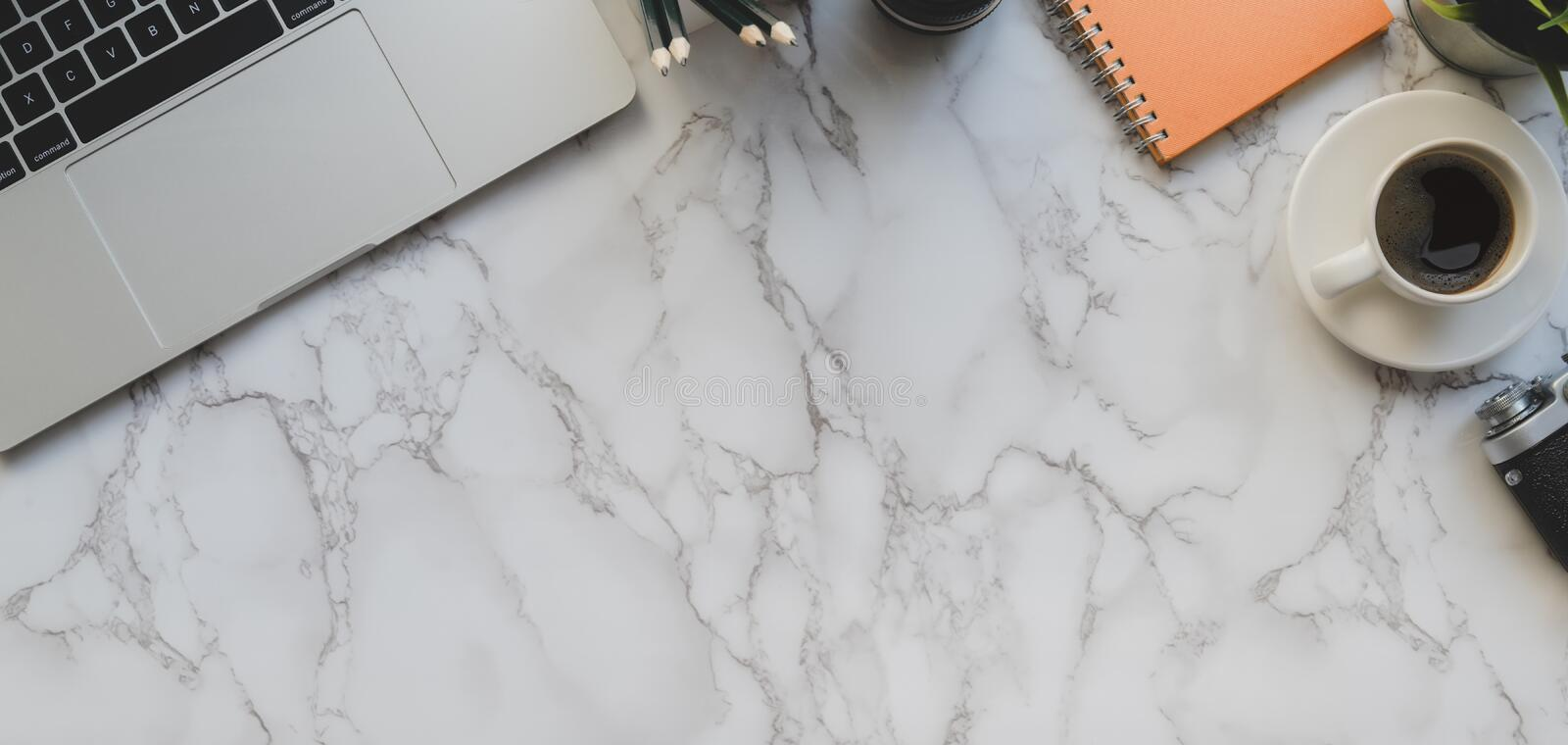 Overhead shot of modern photographer workspace with laptop computer and office accessories on marble stock image
