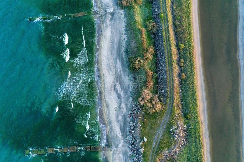 Overhead shot of a narrow shore in the middle of the sea with pathway and greenery on it stock images