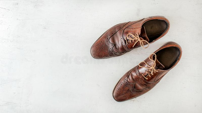 Overhead shot, pair of old worn brown shoes on white board, wide banner with space for text left.  royalty free stock photography