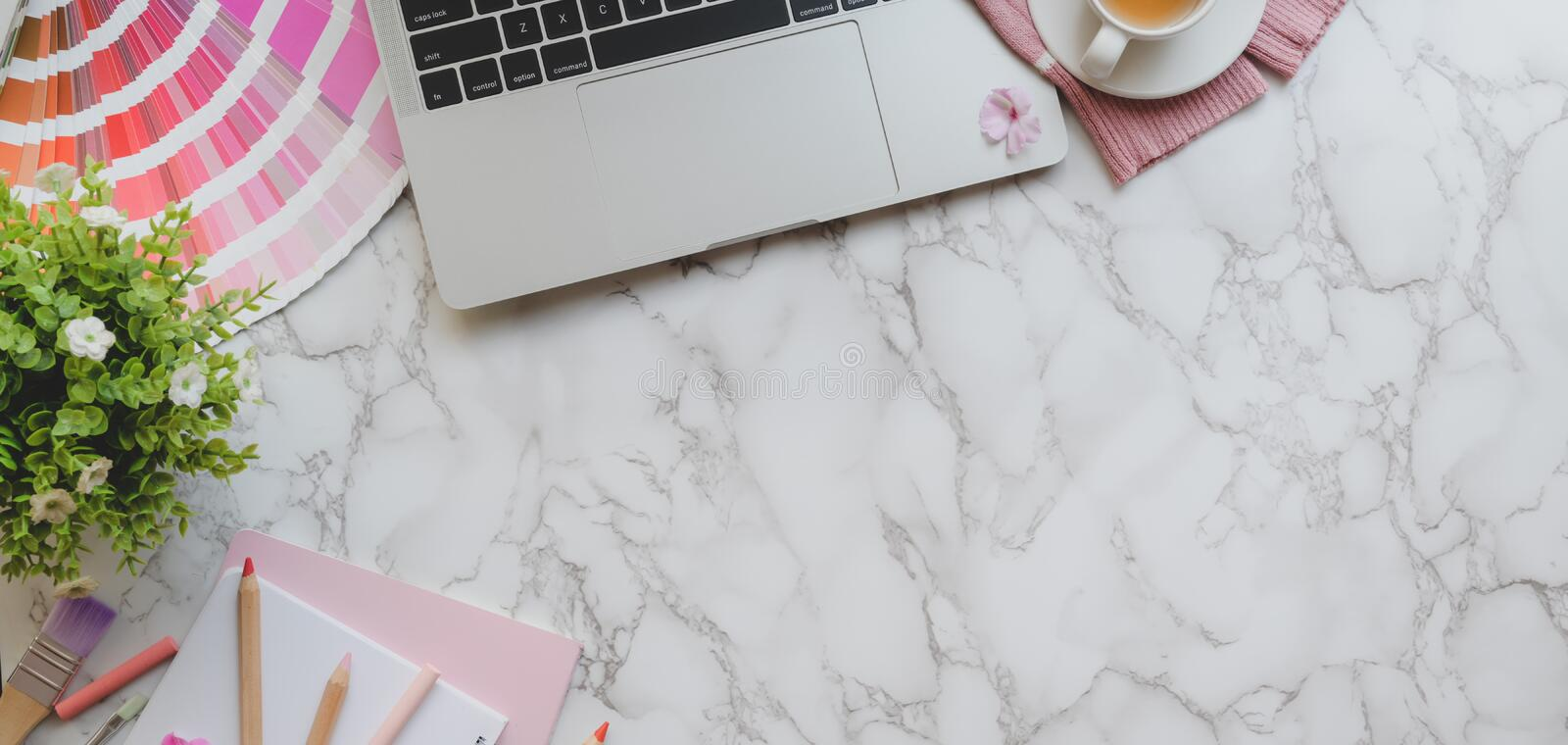 Overhead shot of pink feminine designer workspace with laptop computer and painting tools on marble desk royalty free stock image