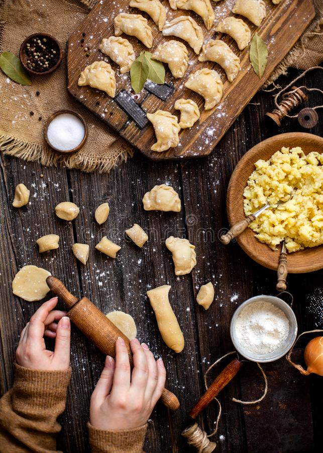 Overhead shot process of making homemade dumplings with potato in women`s hands on rustic wooden table. And boards with plate of mashed potato, spoons, onion stock images