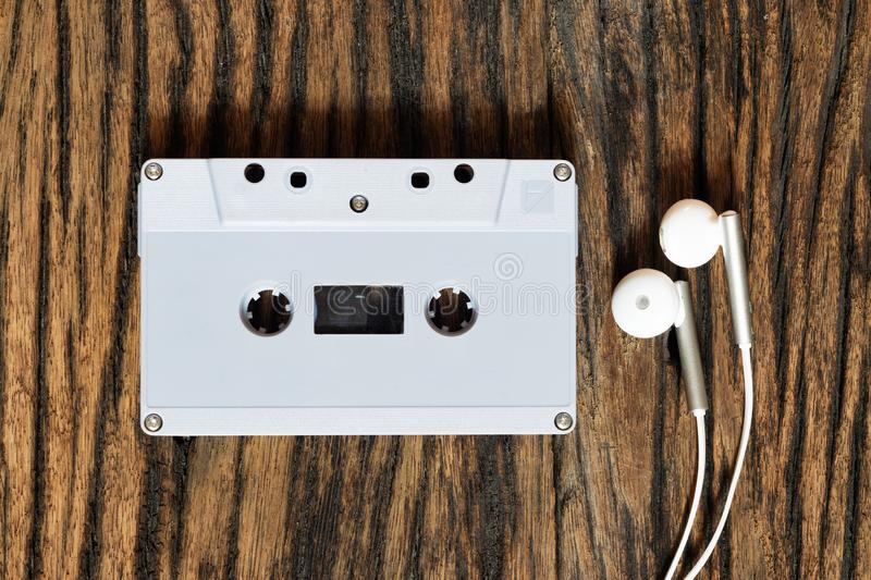 Overhead shot of retro old audio cassette tape with earphone on grunge vintage wood background, top view royalty free stock photography