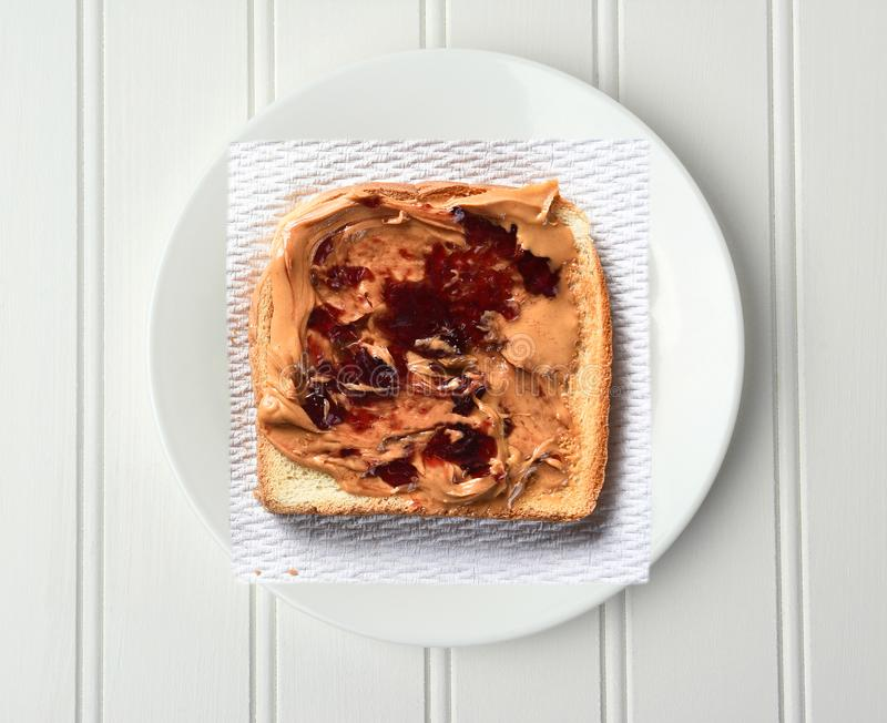 Overhead shot of a slice of toast with Peanut Butter and Jelly, on a paper napkin and white plate stock photos