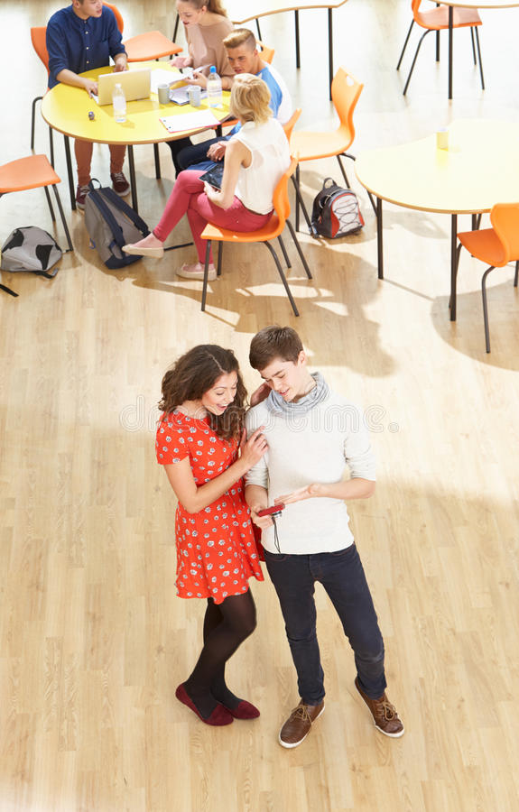 Overhead Shot Of Student Couple Standing In Cafeteria. On There Phones royalty free stock image