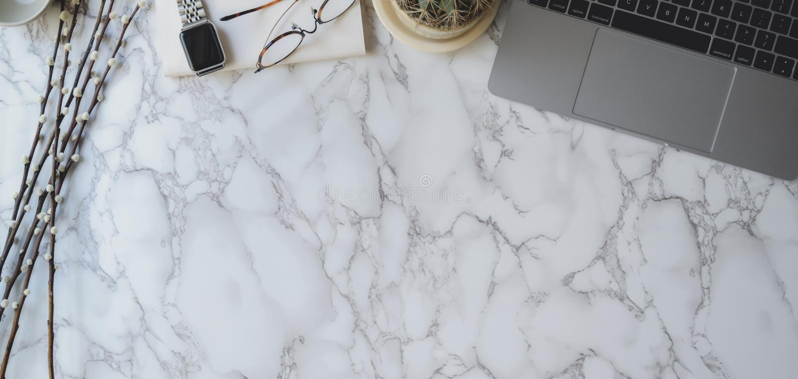 Overhead shot of stylish workspace with laptop computer, smartphone and office supplies on marble desk royalty free stock photos