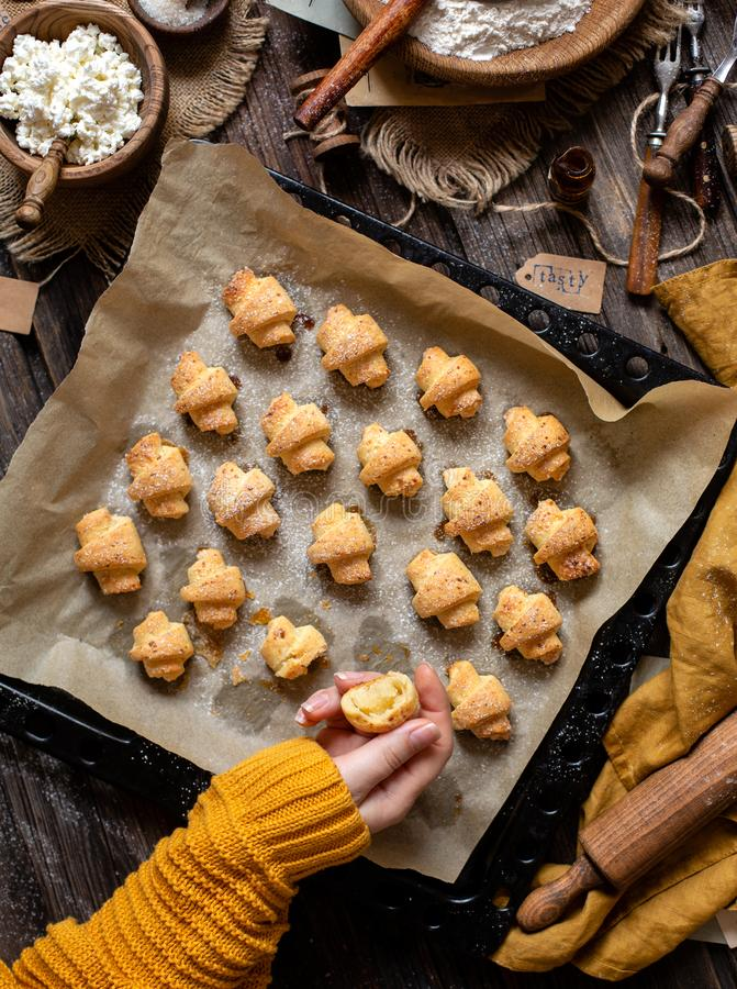 Overhead shot of tasty baked rolled or bagels cookies on baking tray with parchment. In woman hands on rustic wooden table with bowls of flour, sugar and royalty free stock photos